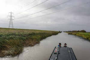 Heading towards Welney on the Old Bedford river in November 2016. NB Olive Emily is about to run into a mass of cott weed and an undredged length of the river that runs beneath the power cables three miles from Salters Lode. This is evident from the uncovered section of bank underneath the pylons and the continuation of dredging further along towards Welney and Welched Dam lock.